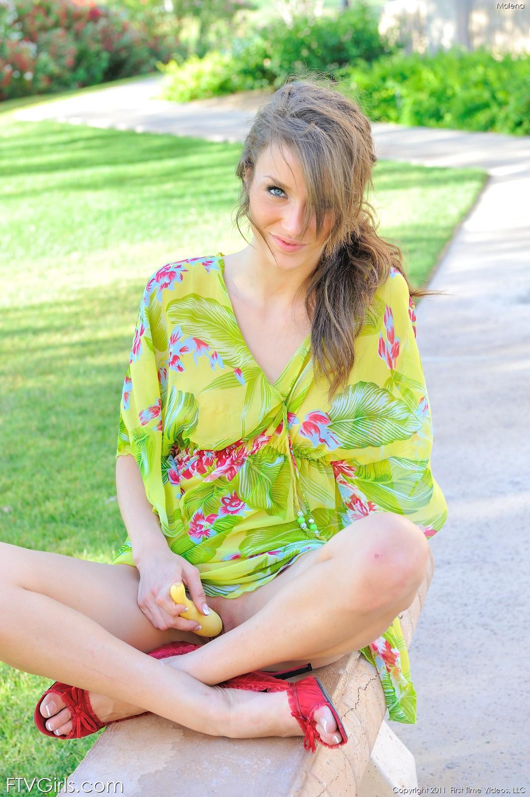 Malena Morgan в красных туфляк и зеленом платье сует игрушку в свои сиськи на скамейке в парке