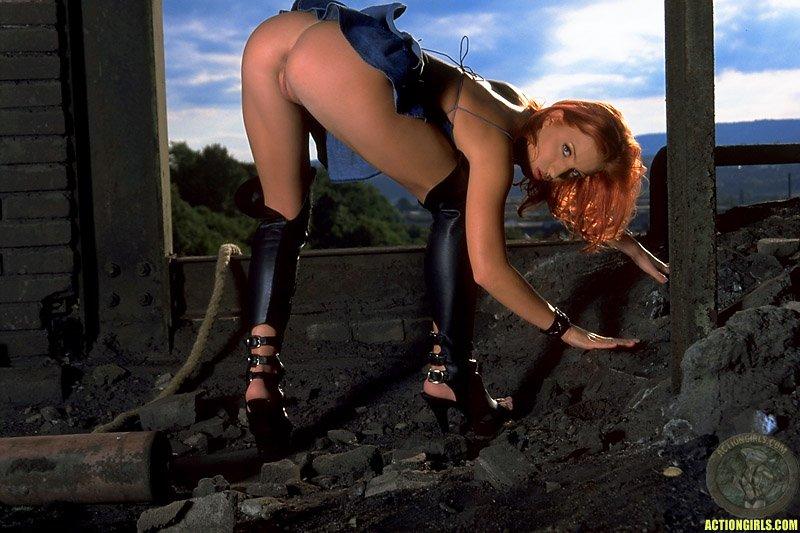 Рыженькая Эшли Роббинс в темных сапожках на высоком каблуке и голубой юбке забавляется