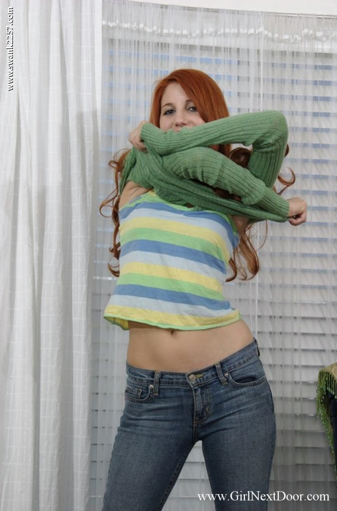 Красивая рыжая Rita Lovely обнажает гладкую пилотку после того как стаскивает джинсы и голубое интимное белье